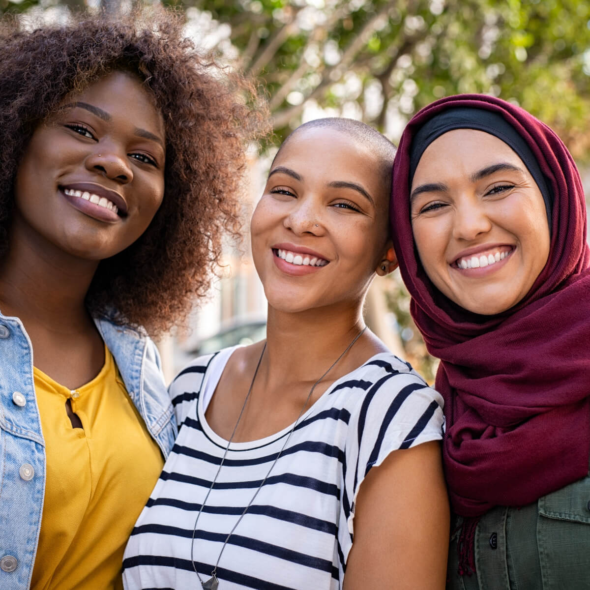 Portrait of three multi-ethnic female friends smiling.