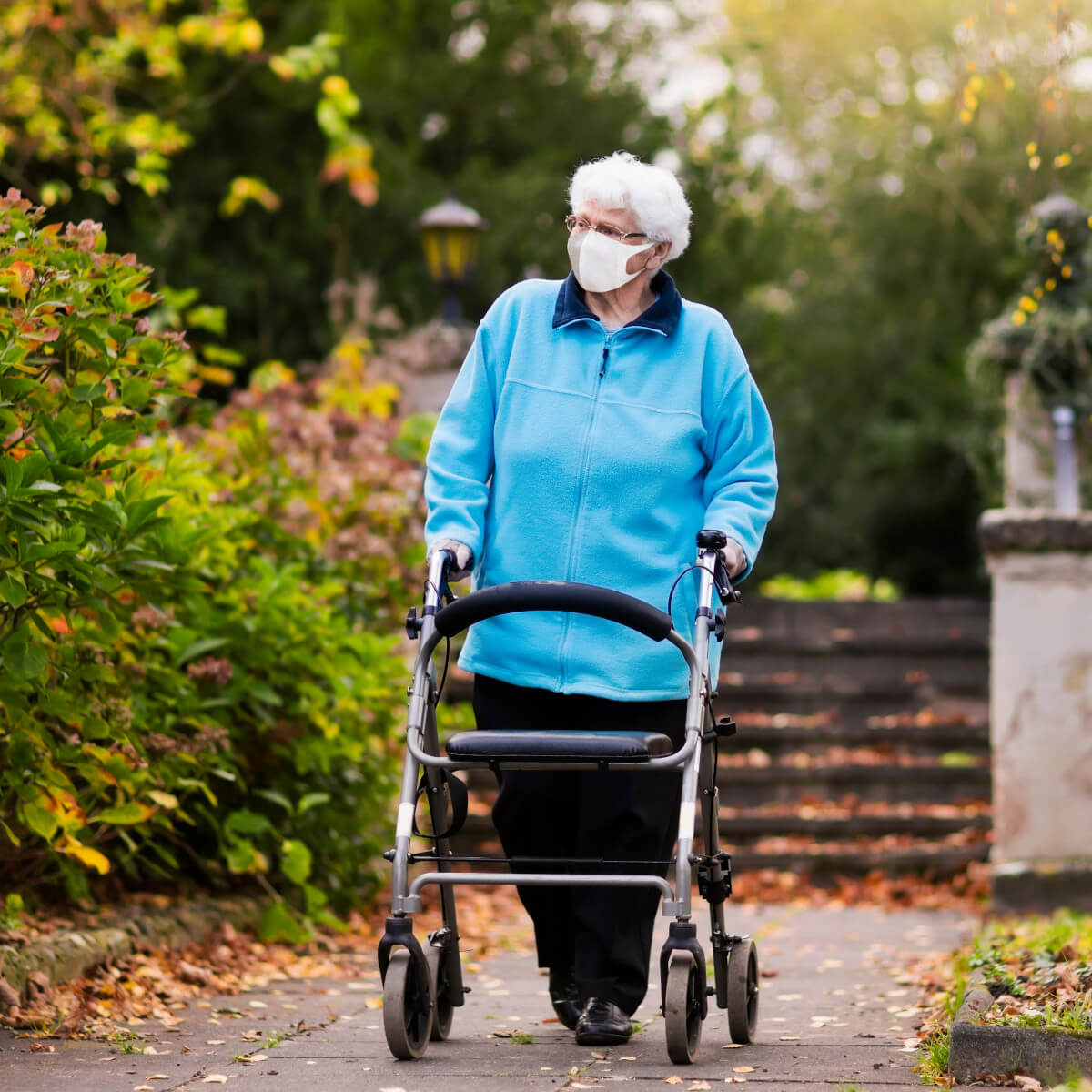 Elderly woman wearing a mask pushes her walker through a park