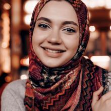 Beautiful an Arabian girl with a headscarf on her head posing in a cafe, looking at the camera and smiling