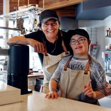 Smiling man and a person with a disability working behind the counter of a coffee shop
