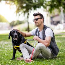 Young blind man with white cane and guide dog sitting in a city park