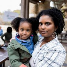Young woman holds daughter and looks at camera with urban outdoor health clinic in background