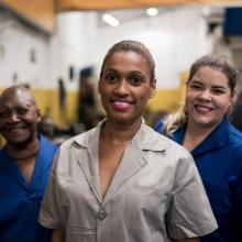 Group of smiling female mechanics in an auto repair shop