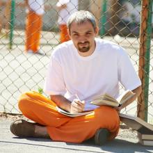 Prison inmate sitting on the ground writing in notebook and holding book