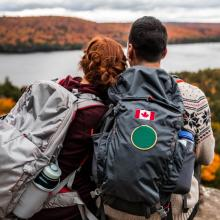 Young couple sit on rock looking at view of the fall colours and river. Canada