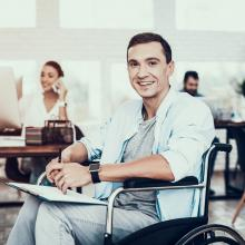 Disabled man in wheelchair at work in an office with coworkers in background. Accessibility