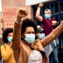 A black woman wearing a protective mask with other people protesting against racism